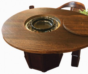 Egg-shaped IRORI dining table with wedge clamp made of Paulownia wood fired on surface